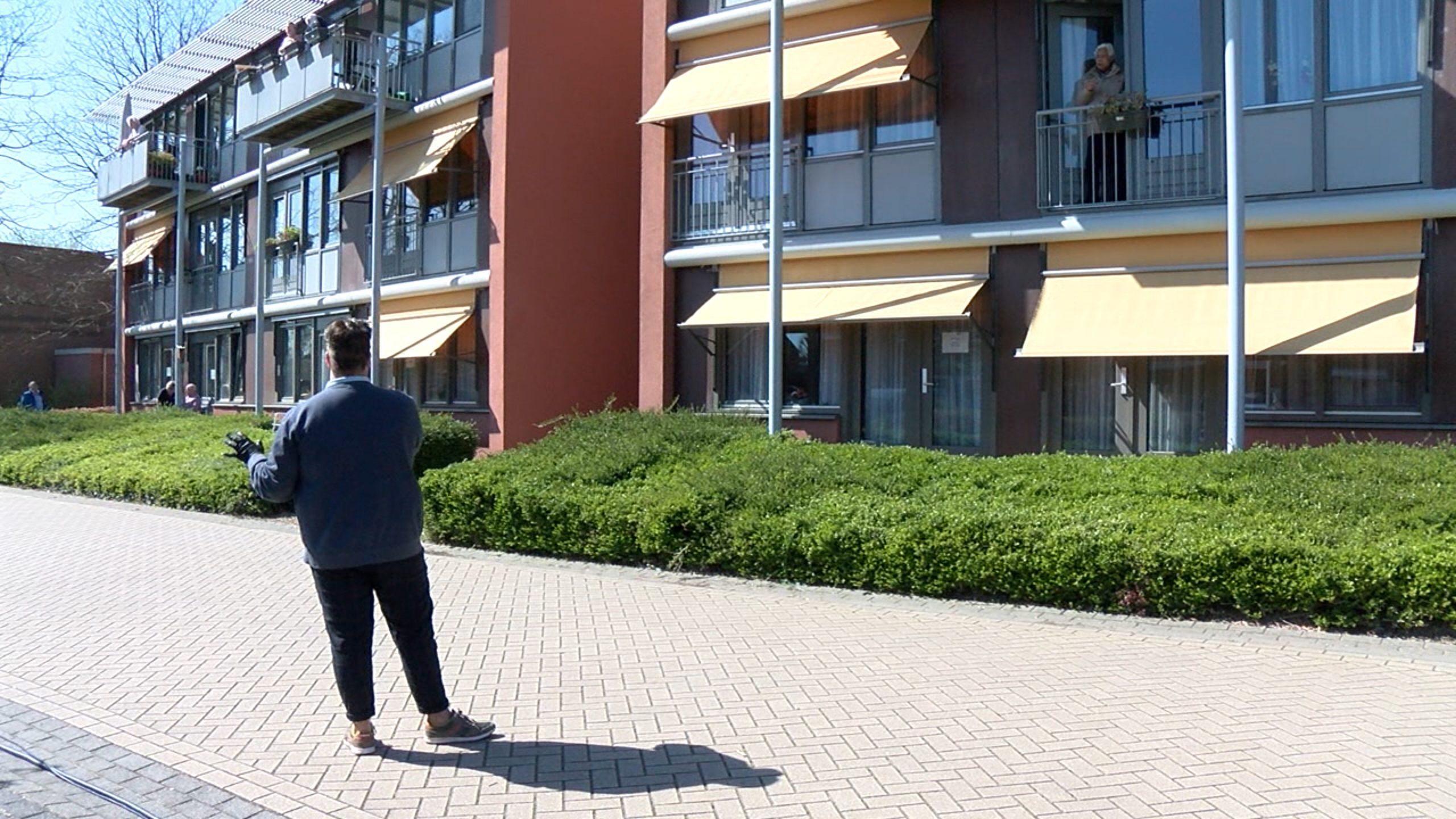 Ouderen volgen optreden vanaf balkon